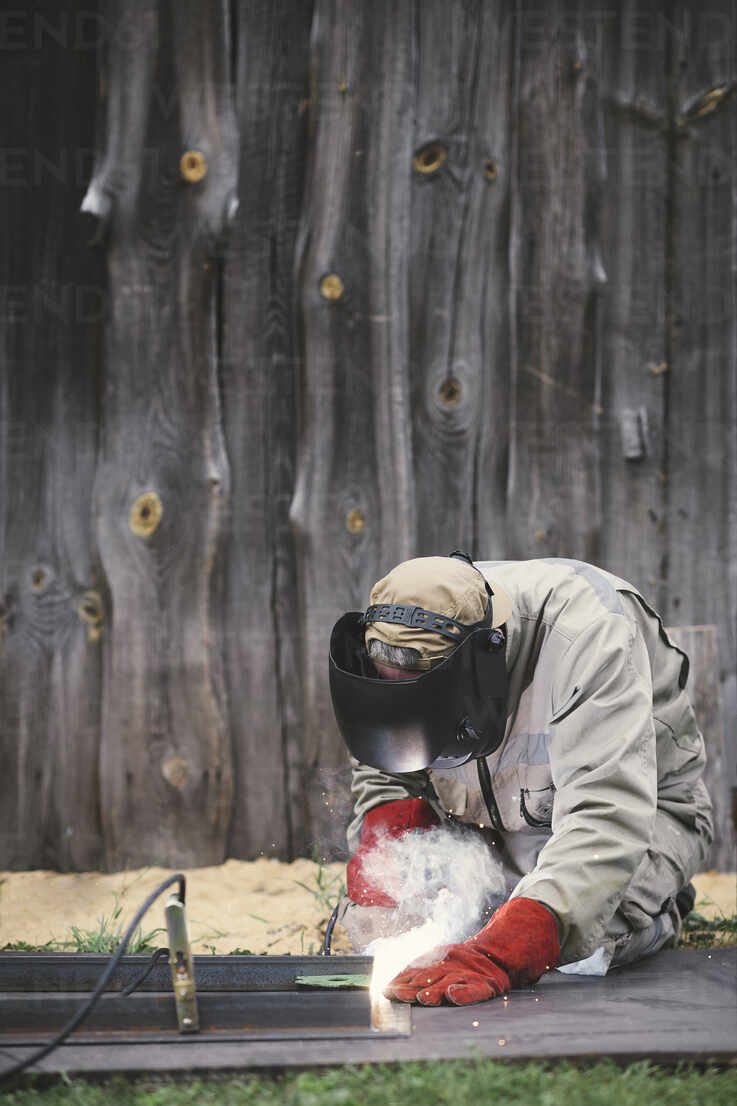 Man welding metal in his backyard - EYAF00359 - Ekaterina Yakunina/Westend61