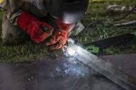 Man welding metal in his backyard - EYAF00362