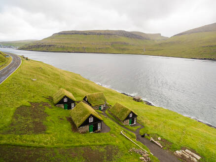 Aerial view of lonely group of houses near a lake, Faroe island - AAEF01328