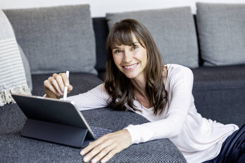 Portrait of smiling woman using tablet in living room at home - FMKF05837