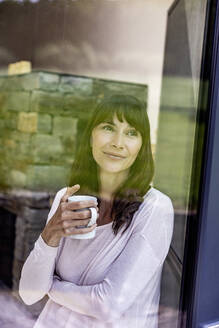 Portrait of smiling woman holding cup of coffee at home - FMKF05840