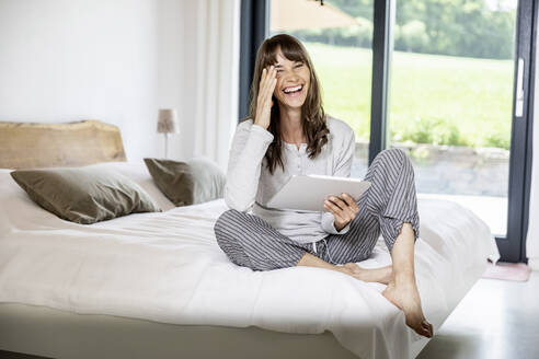 Laughing woman with tablet sitting on bed at home - FMKF05843