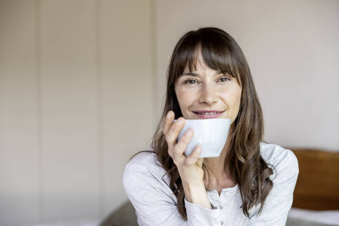 Portrait of relaxed woman holding cup of coffee at home - FMKF05849