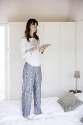 Woman standing on bed at home using tablet - FMKF05852