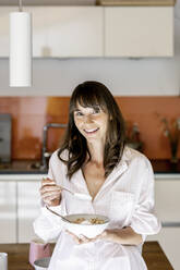 Portrait of woman wearing pyjama eating muesli with yogurt in kitchen at home - FMKF05858