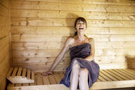 Portrait of laughing woman in a sauna - FMKF05867