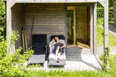 Woman relaxing on a lounge outside sauna - FMKF05873
