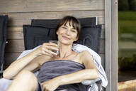 Portrait of woman relaxing on a lounge holding glass of water - FMKF05876