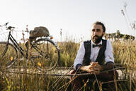 Well dressed man sitting on a wooden walkway in the countryside next to a bike - JRFF03590