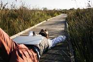 Well dressed man with laptop lying on a wooden walkway in the countryside - JRFF03602