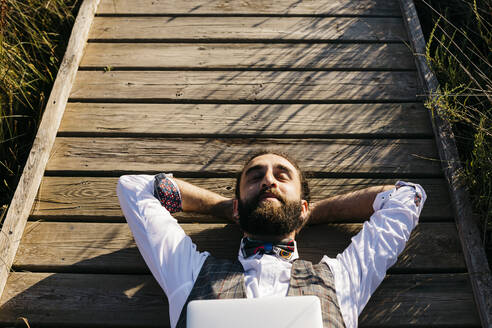 Well dressed man with laptop lying on a wooden walkway in the countryside - JRFF03605