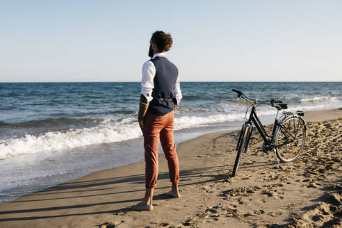 Well dressed man with his bike standing on a beach - JRFF03623