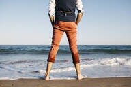 Rear view of well dressed man standing on a beach at water's edge - JRFF03632