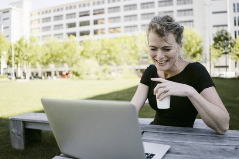 Portrait of smiling mature businesswoman with laptop and coffee to go outdoors - KNSF06194
