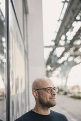 Portrait of content man wearing glasses looking at distance - KNSF06206