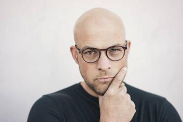 Portrait of starring bald man wearing glasses - KNSF06209