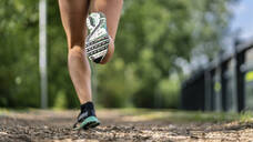 Feet of a young woman jogging on a woodchip trail - STSF02182