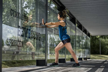 Young sportive woman wearing headphones and making stretching exercise - STSF02188