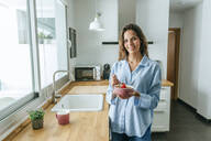 Portrait of young woman wearing pyjama eating muesli in kitchen at home - KIJF02529