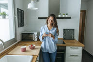 Young woman wearing pyjama in kitchen at home using cell phone - KIJF02532