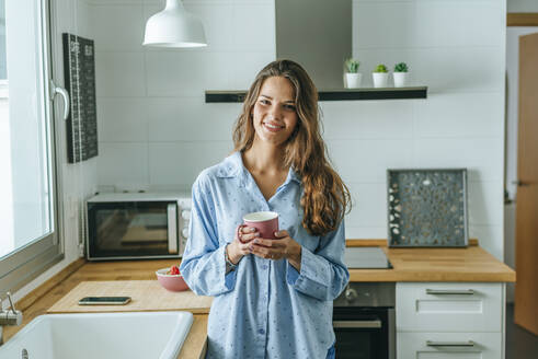 Portrait of smiling young woman with cup of coffee wearing pyjama in kitchen at home - KIJF02535