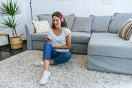 Laughing young woman sitting on floor in living room listening to music with cell phone - KIJF02544