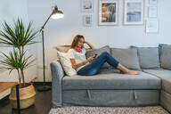 Young woman on sofa with headphones and cell phone - KIJF02547
