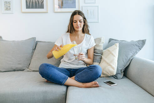 Young woman sitting on sofa pouring orange juice in glass - KIJF02553