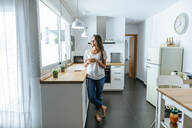 Young woman standing in the kitchen with glass of orange juice - KIJF02556