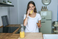Young woman having breakfast with juice and croissant in the kitchen - KIJF02559