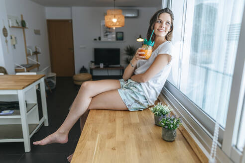 Smiling young woman sitting on kitchen counter with a drink looking out of window - KIJF02583