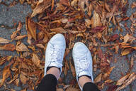 Low section of woman wearing white shoes standing on autumn leaves - JUNF01722