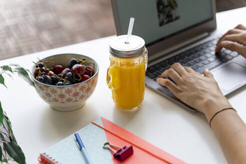 Close-up of woman using laptop at desk with orange juice and fruit - AFVF03719