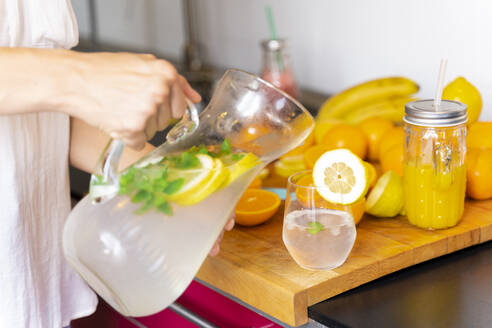 Close-up of woman in kitchen at home pouring lemonade into glass - AFVF03746