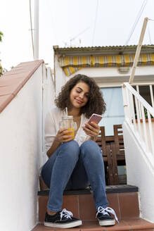 Smiling young woman sitting on stairs with cell and orange juice - AFVF03749
