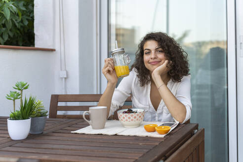 Portrait of smiling young woman with orange juice on balcony - AFVF03755