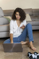 Young woman using cell phone and laptop at home - AFVF03761