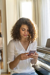 Young woman using cell phone at the piano at home - AFVF03782