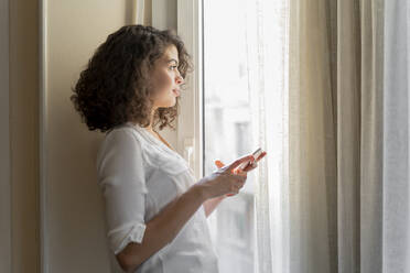 Young woman with cell phone looking out of window at home - AFVF03785
