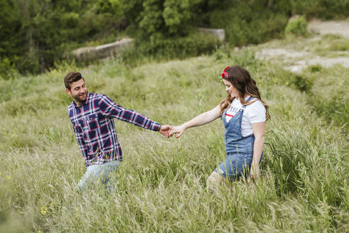 Young couple walking over a meadow holding hands - LJF00626