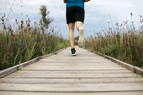 Rear view of a male jogger running on a wooden walkway - JRFF03656