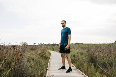 Jogger with earphones and smartphone standing on a wooden walkway - JRFF03659