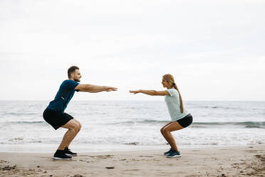Young couple during training on the beach - JRFF03671