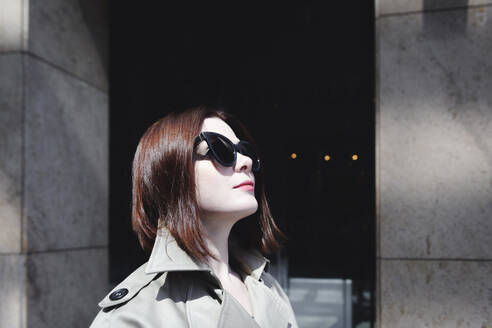 Portrait of a stylish woman with sunglasses and trenchcoat - EYAF00373