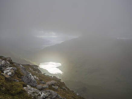 High angle view of lake amidst mountains against cloudy sky during foggy weather, Scotland, UK - HUSF00057