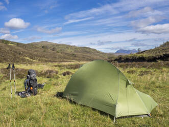 Tent on grassy land against blue sky during sunny day, Scotland, UK - HUSF00066