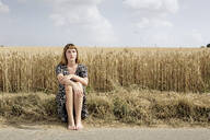 Portrait of young woman sitting barefoot at roadside in front of grain field - FLLF00271