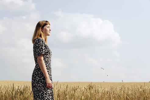 Deutschland,NRW,Ruhrgebiet,Stadt Essen,junge Frau mit Blumenkleid in einem Getreidefeld - FLLF00274