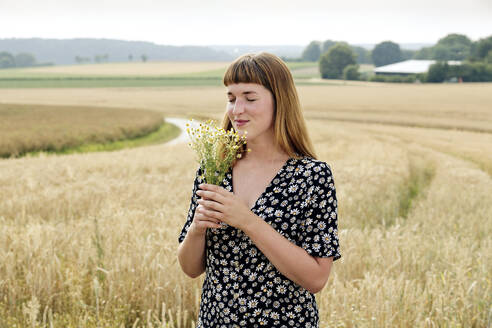 Portrait of smiling young woman with eyes closed smelling bunch of chamomile flower in nature - FLLF00277
