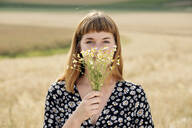 Portrait of young woman with bunch of chamomile flower - FLLF00280